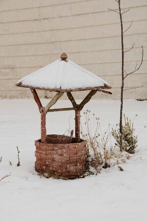 Wooden wishing well in snowy winter scene Banco de Imagens