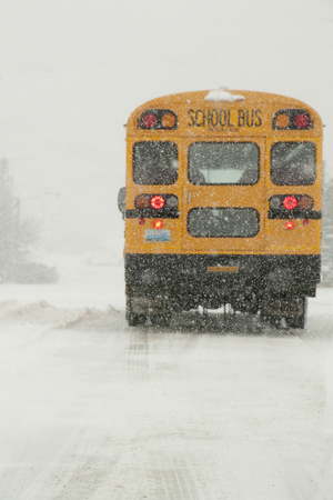 stopped: school bus stopped at stop sign on snowy winter day Stock Photo