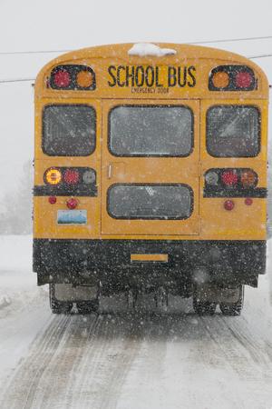 Schoolbus rijden in de besneeuwde winter scène op ijzige weg