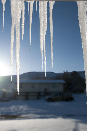 Icicles hanging from roof with neighbors in backdrop