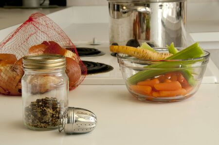 Ingredients for making soup, spices, onions, parsnips, celery, pot all placed on the kitchen counter top