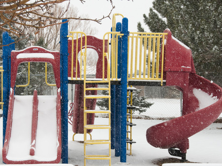 Playset in winter, snow falling and no children to play, slide, monkey bars and ladder