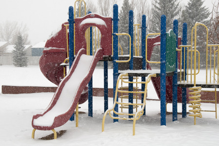 Playset in winter, snow falling and no children to play Banco de Imagens