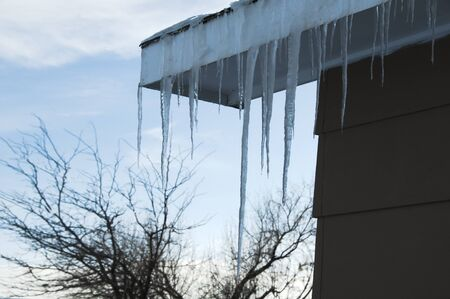 Icicles hanging from rooftop with tree and sunset in spring winter scene