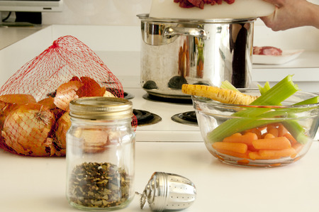 stove top: Ingredients for making soup, spices, onions, parsnips, celery,beef , pot all placed on the kitchen counter top and stove top Stock Photo