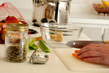 Ingredients for making soup, spices, onions, parsnips, celery, pot all placed on the kitchen counter top; cutting carrots on counter top before adding to pot