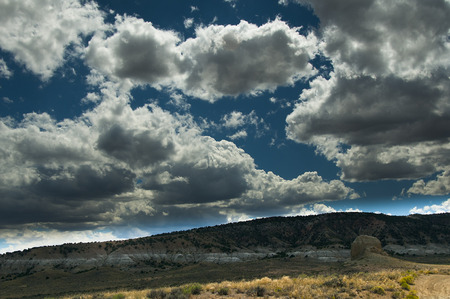 wind blown: Wind blown summer day, with fluffy bright clouds passing overhead, sanstone rock formation Stock Photo