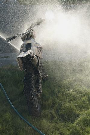 dirt bike: Washing muddy dirt bike with spray of water Stock Photo