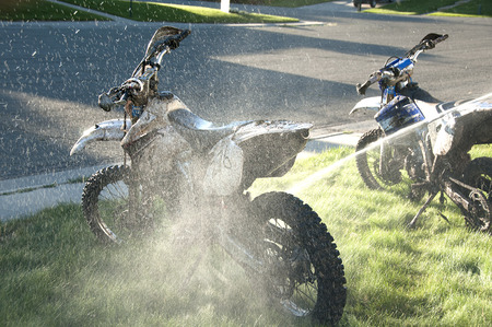 dirt bikes: Washing muddy dirt bikes with spray of water in front yard, lawn Stock Photo