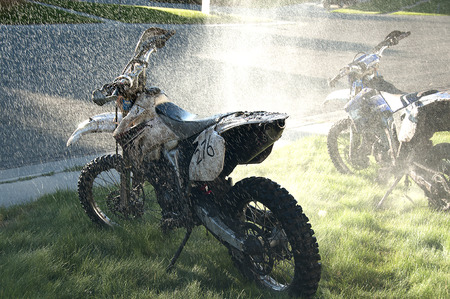 dirt bikes: Washing muddy dirt bikes with spray of water Stock Photo