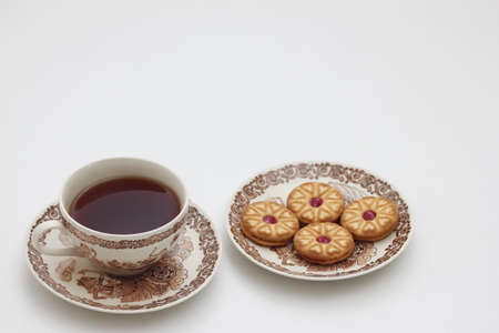 A cup of tea in chinaware and small plate of cookies photo