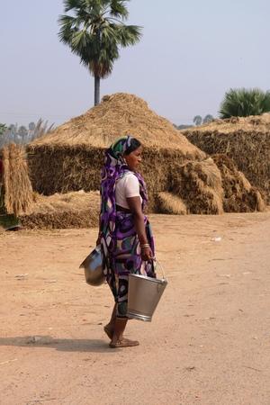 gaya: BODH GAYA, BIHAR, INDIA - NOVEMBER 28, 2013: Unidentified Indian woman carries a metal water bucket and a jar in a village near Sujata Kuti, Bodh Gaya.