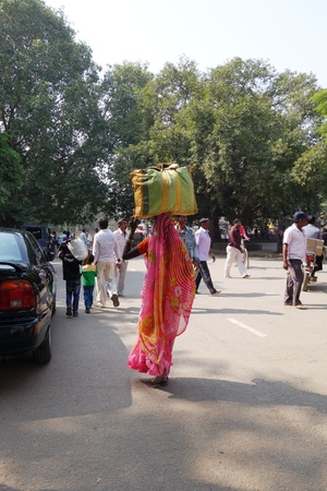 gaya: BODH GAYA, BIHAR, INDIA - NOVEMBER 23, 2013: Unidentified Indian woman carries a big bag on her head in Bodh Gaya, India.  Carrying on the head is a common practice in India.