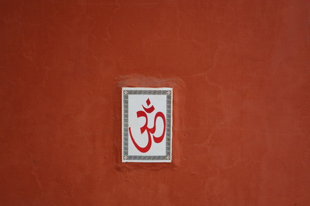 exposed concrete: Terracotta wall with Hindu Om symbol, India Stock Photo