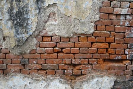 pared rota: Pared de ladrillo vieja dañada parcialmente en la India