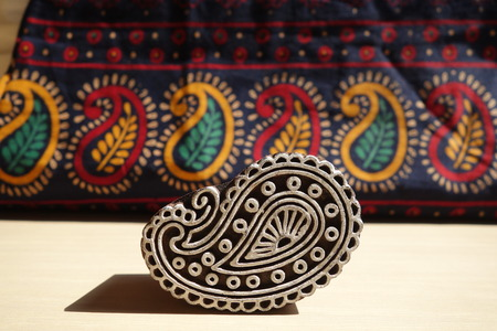 Indian wood printing block with block printed textile background