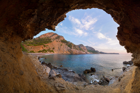 Coll Baix beach near Alcudia, Mallorca, Spain during pink pastel sunrise in a creative made cave. Calm remote beach on Majorca, Balearic Islands. Banque d'images - 113477335