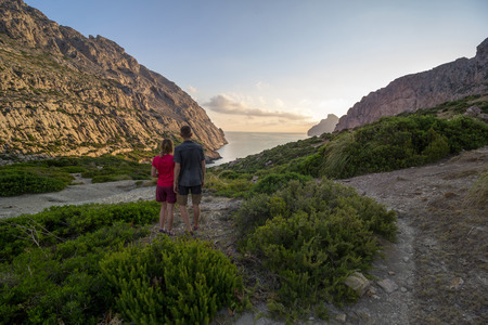 Young couple standing and smiling in front of sunrise over mountains and beaches of Mallorca, Spain