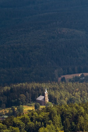 Church in mountain village lit by sun coming through clouds in Poland