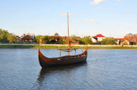 reconstruct: Reduced copy of Drakkar Vikings of the IX century Yatvagi on the lake in the city of Lida. Belarus Editorial