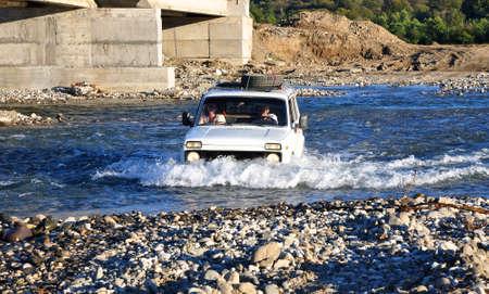 4x4: White Russian Lada 4x4 SUV overcomes a water barrier