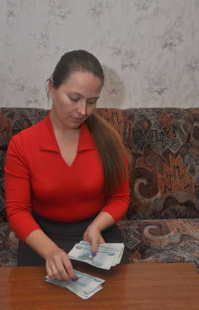 A young woman sits at a table in a room and considers Russian money Фото со стока