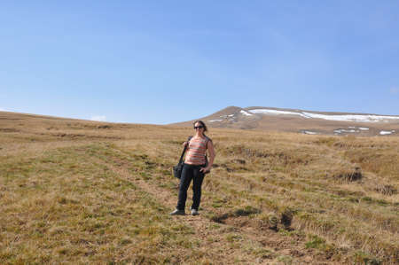 A young woman stands on the Lagonaki plateau in front of the Abadzesh mountain. Caucasian Reserve, Russia