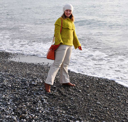 Young woman in autumn clothes standing by the sea. Sochi, Russia 写真素材