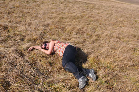 Young woman with glasses lying on the dry grass