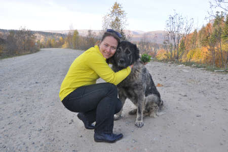 Young woman hugging a caucasian shepherd on a dirt road 写真素材