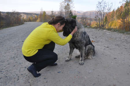 A young woman and a Caucasian shepherd sitting on a dirt road and hugging