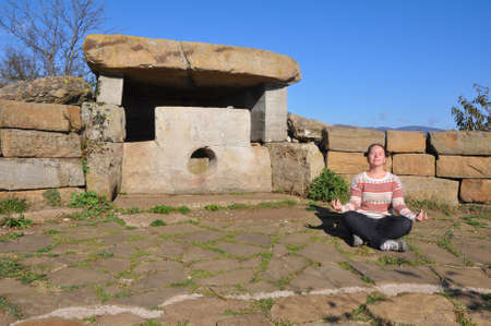 A woman meditates near the dolmen on the Nexis ridge. Russia, the neighborhood of Gelendzhik 写真素材