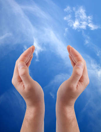 Cupped hands isolated on sky background photo