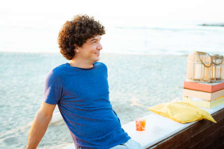 curly caucasian latino man enjoing a drink at sunset on the beach smiling.concept about joy and happiness to tast a cocktail on a warm sunny summer day on a bench Standard-Bild