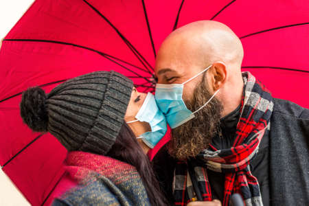 isolated close up portrait of a young adult couple kissing each other with passion wearing protective face mask.hipster man and caucasian woman wearing warm winter clothes in love.new normal lifestyle