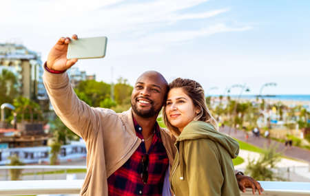 young interracial couple of a bald black man and a caucasian woman taking a self picture on the coastline.selfie time during winter holidays on seaside.concept about tech, lifestyle and social media influencer Banco de Imagens
