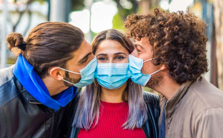 close up portrait of two man and a caucasian woman kissing each other wearing protective face mask outdoor after coronavirus lockdown reopening holidays.friends in a sweet moment.new normal lifestyle Stock fotó