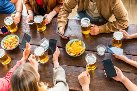 Multiracial group of friends enjoying a beer in a bar restaurant.Young people hands holding a beer and smartphone cheering.Friendship and youth life.tech, joy, togetherness concept.Up view with no faces Zdjęcie Seryjne