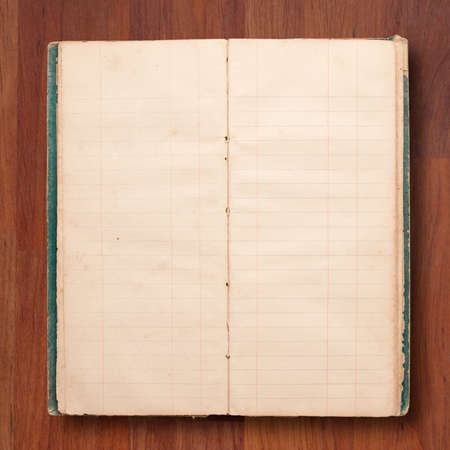 Open blank page of old notebook on wood background