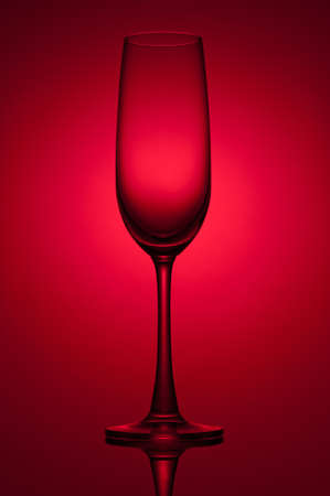 Empty champagne glass on red background