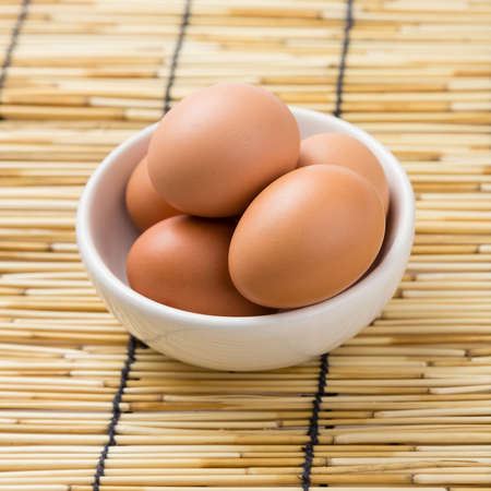 Eggs in white bowl on the bamboo background