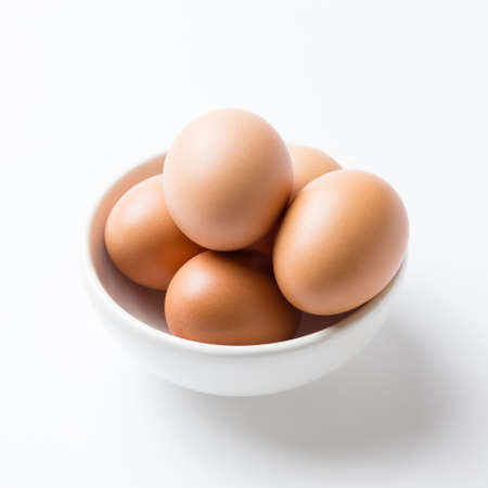 Eggs in white bowl on the white background Stock Photo