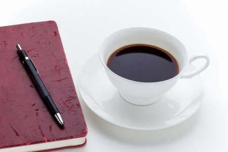 Coffee cup and grunge red notebook on white background