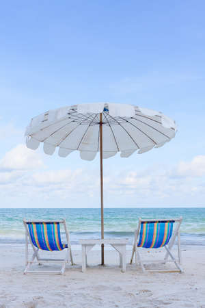 Beach Chair and white umbrella against the sea