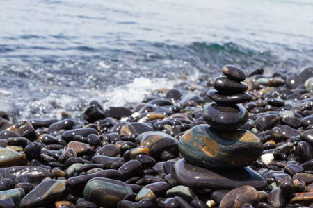 Stones pyramid on stone beach symbolizing zen