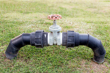 Valve on the grass for control used water in the park Stock Photo
