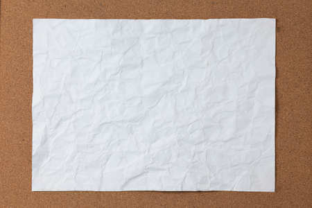 Crumpled white paper on cork board background Stock Photo