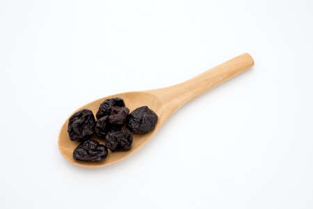 Plum in a wooden spoon on white background Stock Photo