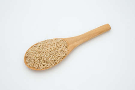 Brown rice in a wooden spoon on white background Stock Photo