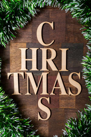 Wooden letters shaped tree forming the word christmas, surrounded with green Christmas garland photo